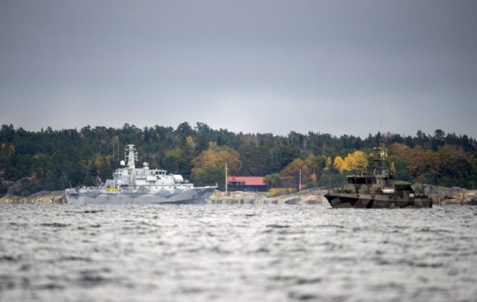 The Swedish minesweeper HMS Kullen and a guard boat are seen in the search for suspected 'foreign underwater activity' at Namdo Bay, Stockholm October 21, 2014. [TT News Agency]