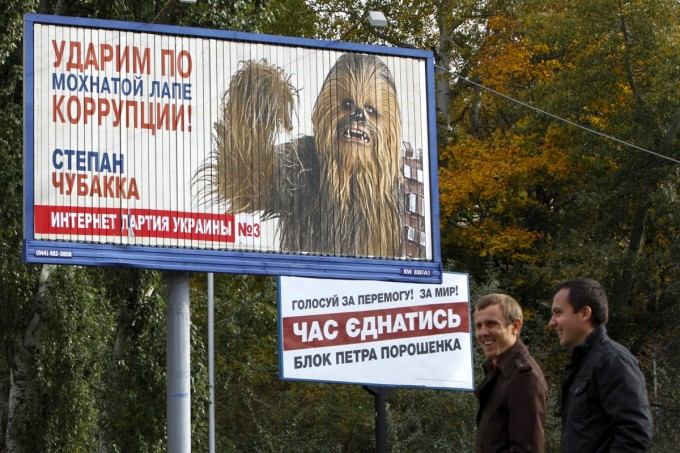 Men walk past a pre-election poster with a portrait of a candidate from the Internet party of Ukraine, Stepan Chewbacca, in the centre of Kiev