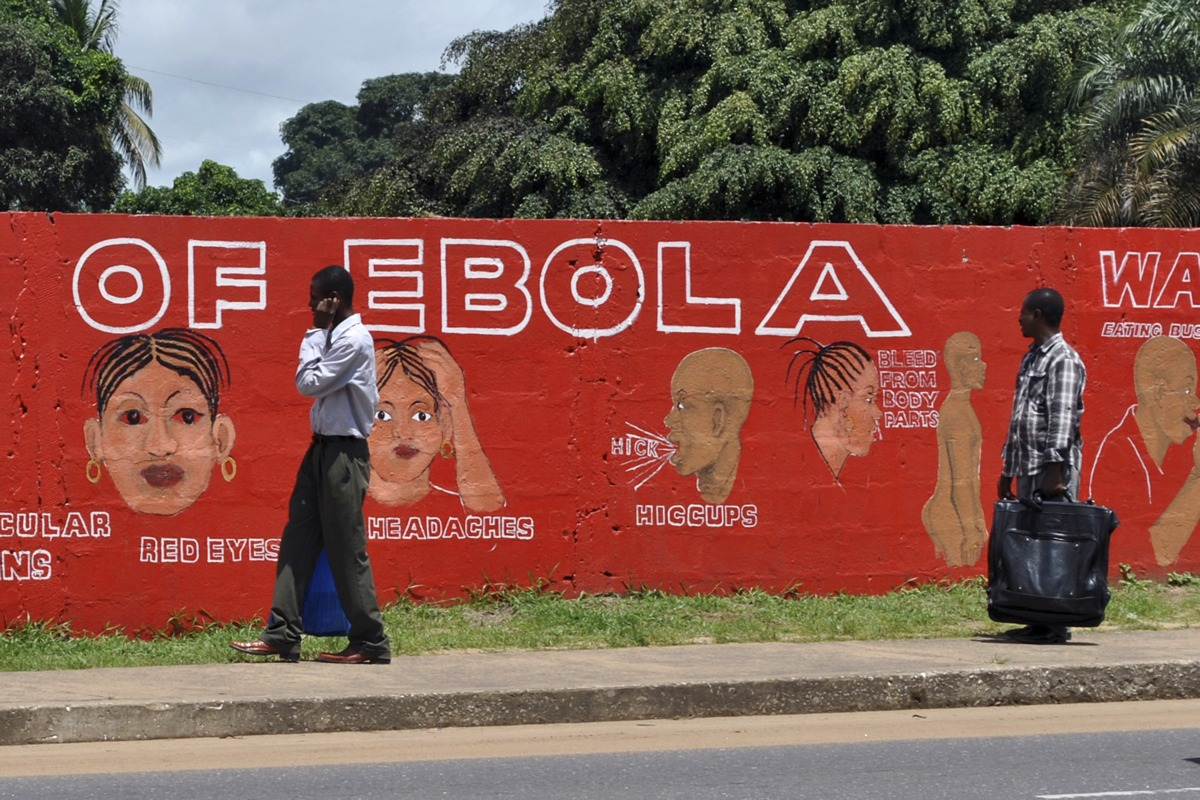 Pedestrians walk past a mural showing the symptoms of the Ebola virus in Monrovia, Liberia, September 26, 2014. [REUTERS/James Giahyue]