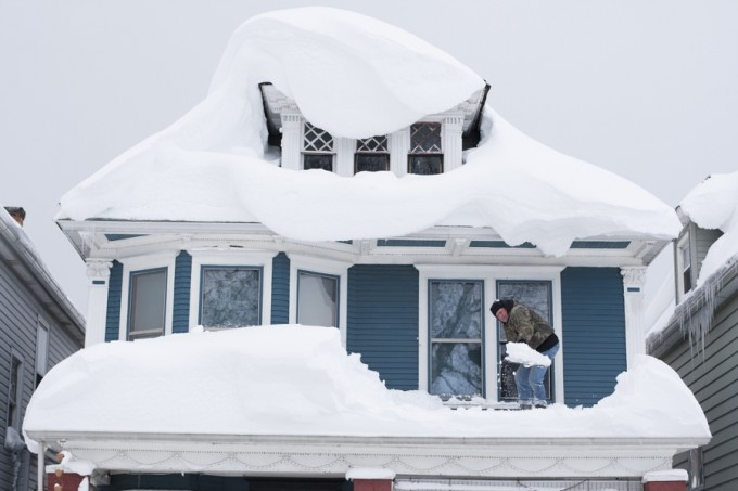 Tom Wilczak shovels snow from the roof of his home following a storm in Buffalo, New York November 20, 2014.   REUTERS/Aaron Lynett