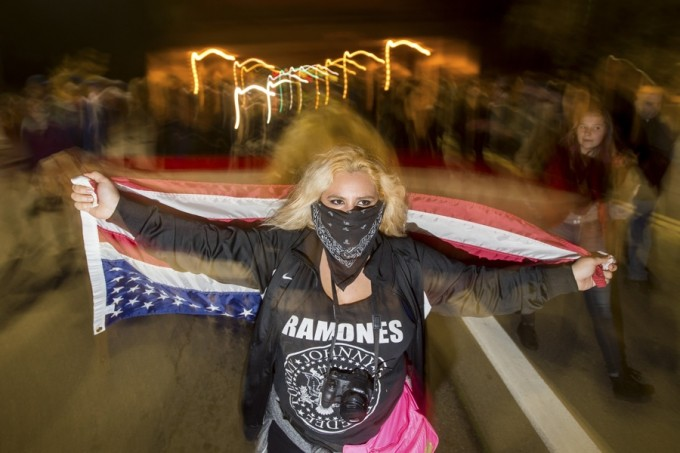 A anti-police protester who declined to give her name marches through Oakland, California December 10, 2014.  REUTERS/Noah Berger