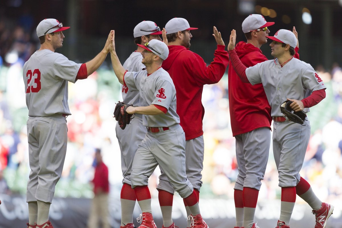 Players on the St. Louis Cardinals baseball team, high-fiving one another in happier, more innocent times. [Reuters]