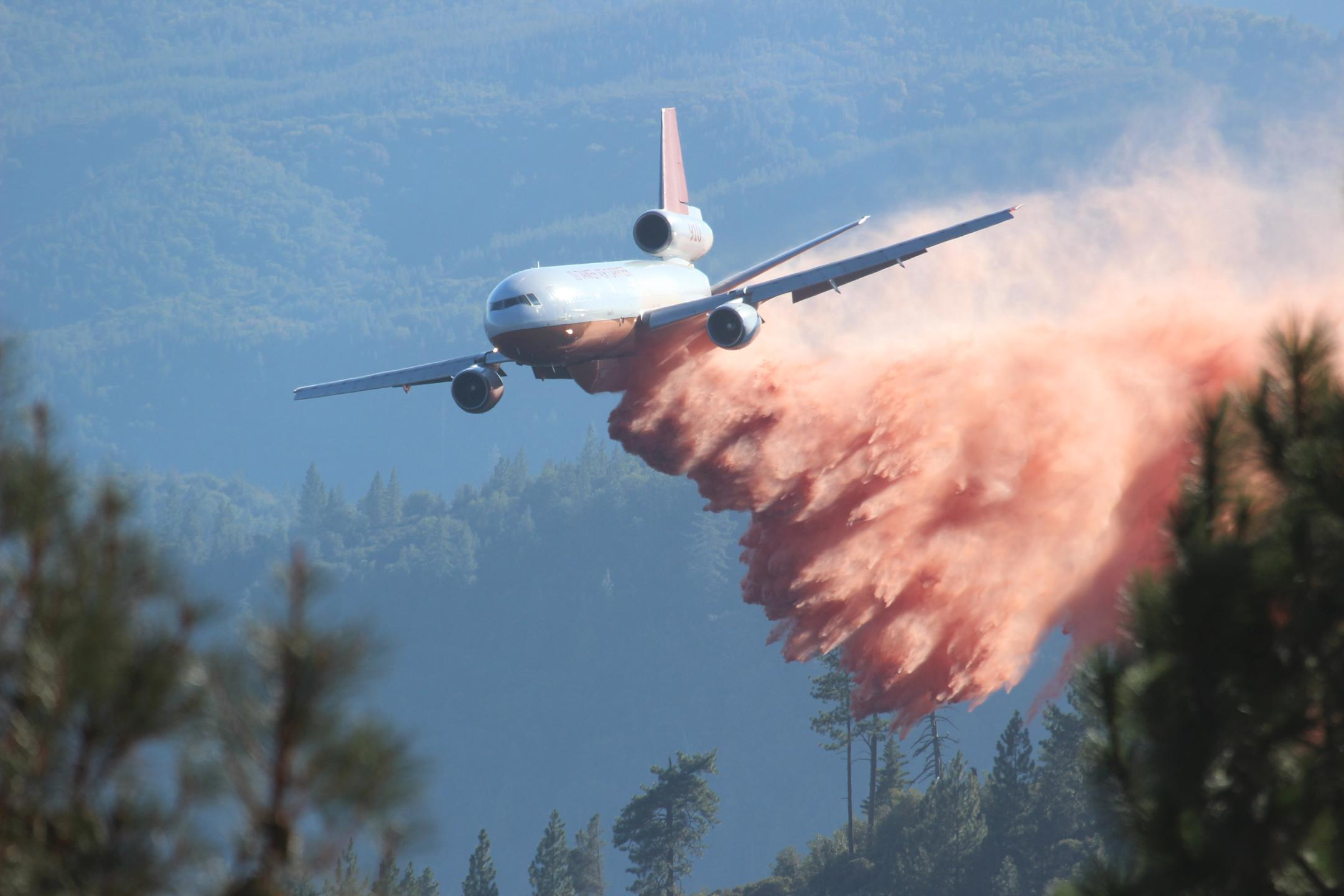 A DC-10 air tanker drops chemical fire retardant below Pilot Peak at the Rim Fire. The Rim Fire in the Stanislaus National Forest near in California began on Aug. 17, 2013 and is under investigation. The fire has consumed approximately 199,237 acres and is 32% contained. U.S. Forest Service photo by Mike McMillan.