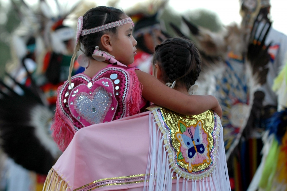 "A pair of young Native American dancers stand together during the opening ""grand entry"" to start the Oglala Nation Pow Wow and Rodeo in Pine Ridge, South Dakota, August 4, 2006. The annual festival is a bright spot for the Pine Ridge Indian Reservation, which struggles with high unemployment and problems with substance abuse and gangs and is one of the poorest communities in the United States. (REUTERS/JONATHAN ERNST)"