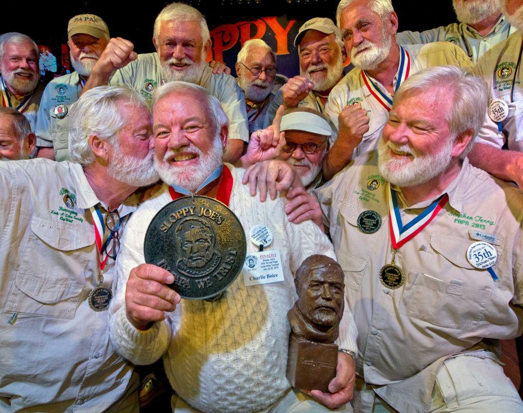 "In this Saturday, July 25, 2015 photo provided by the Florida Keys News Bureau, Charlie Boice, center, is congratulated by previous victors after winning the 2015 ""Papa"" Hemingway Look-Alike Contest at Sloppy Joe's Bar in Key West, Fla. Boice finally won the contest after trying for 15 years, beating out 121 other entrants following two preliminary rounds, a semi-final and two final rounds. The competition was a facet of the island's annual Hemingway Days festival that ends Sunday, July 26. Planting a playful snook on Boice is Wally Cox, left, the 2014 winner. (Andy Newman/Florida Keys News Bureau)"