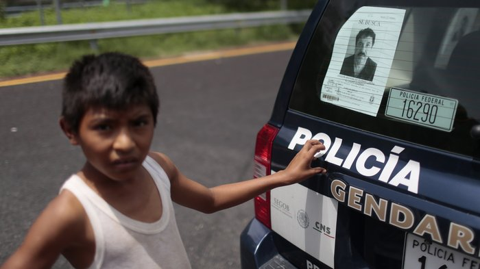 "A boy stands next to a police car with a picture of fugitive drug lord Joaquin ""El Chapo"" Guzman's at a checkpoint on the highway connecting Mexico City and Acapulco, in Guerrero State, Mexico. Pedro Pardo, AFP/Getty via NPR"