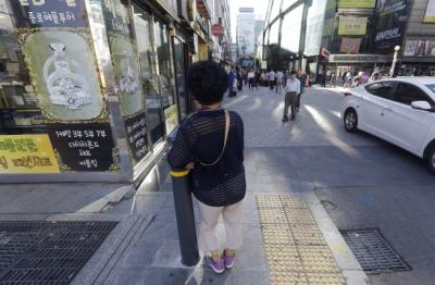 "In this Sept. 17, 2015 photo, an elderly woman stands at a small, bustling plaza in front of the Piccadilly theater in Seoul, South Korea. It's a place where elderly prostitutes openly solicit customers for sex in nearby motels. They are dubbed ""Bacchus ladies"" after the popular energy drink that they have traditionally sold.(AP Photo/Ahn Young-joon)"