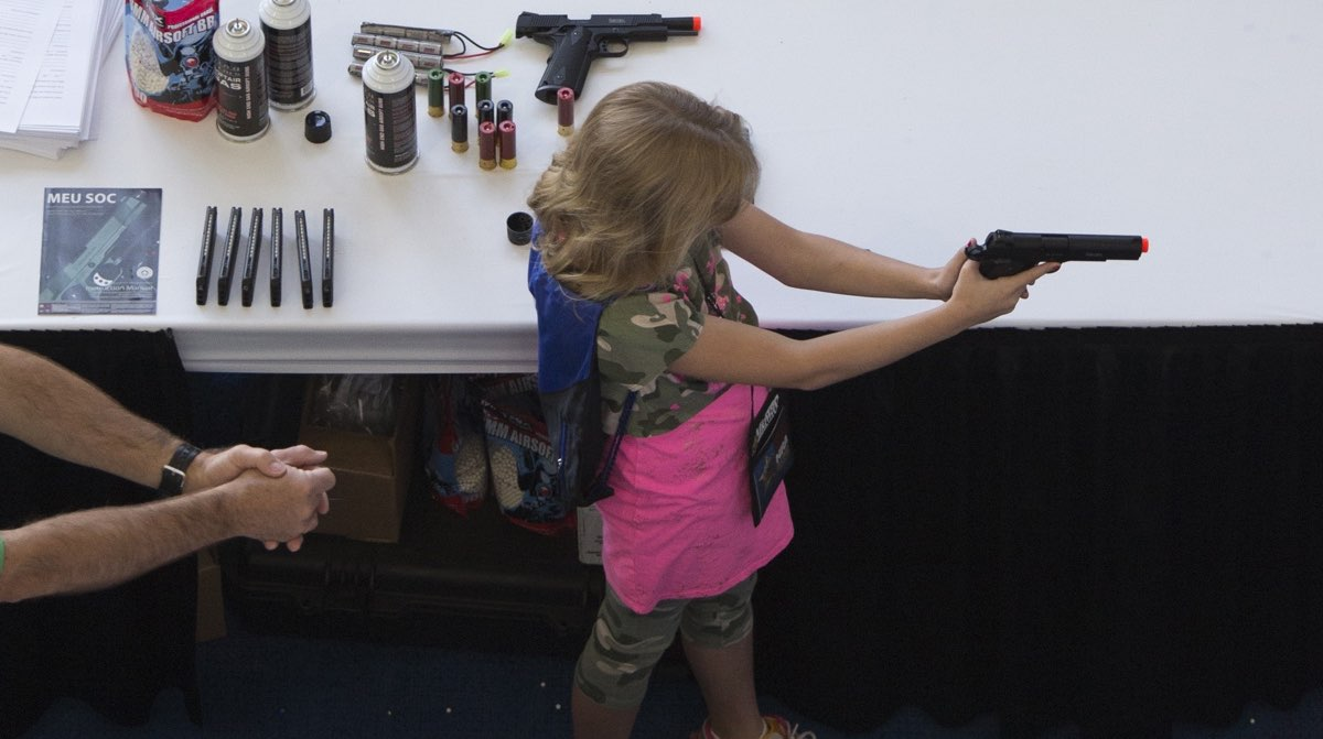 A man shows a girl how to hold an airsoft gun at a 2013 NRA meeting. [Reuters]