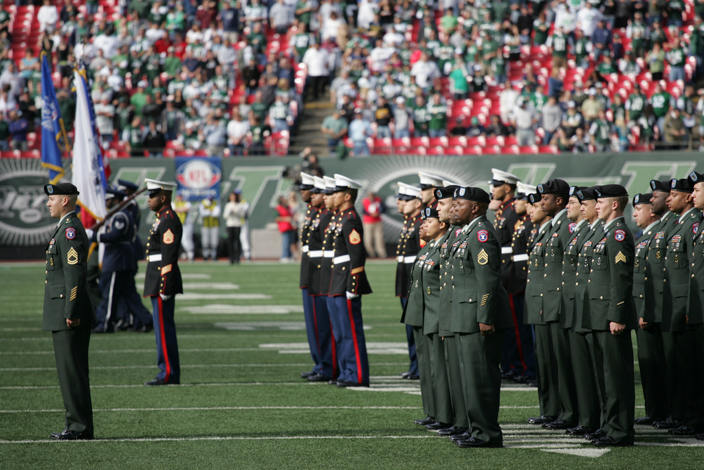 EAST RUTHERFORD, N.J. -- Marine Corps, Air Force, Navy, Coast Guard and Army service members stand at attention and salute during the singing of the National Anthem on the field at Giants Stadium for a pre-game ceremony honoring veterans, Nov. 15. A Coast Guard detachment sang the National Anthem and were joined by a joint-service color guard before the New York Jets game against the Jacksonville Jaguars. Chief Master Sgt. James A. Roy, Chief Master Sergeant of the Air Force, presented the coin for the pre-game coin toss.(Official Marine Corps photo by Sgt. Randall A. Clinton)