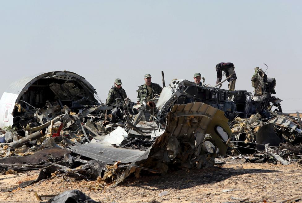 Russian Military investigators stand near  debris of a Russian airliner at its crash site in north Egypt, Nov. 1, 2015. REUTERS