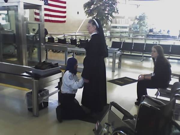Catholic nun being frisked by a Muslim security agent