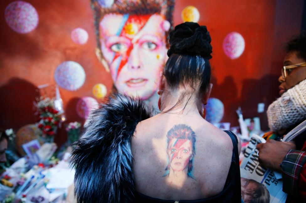 A woman with a Ziggy Stardust tattoo visits a mural of David Bowie in Brixton, south London, January 11, 2016. REUTERS