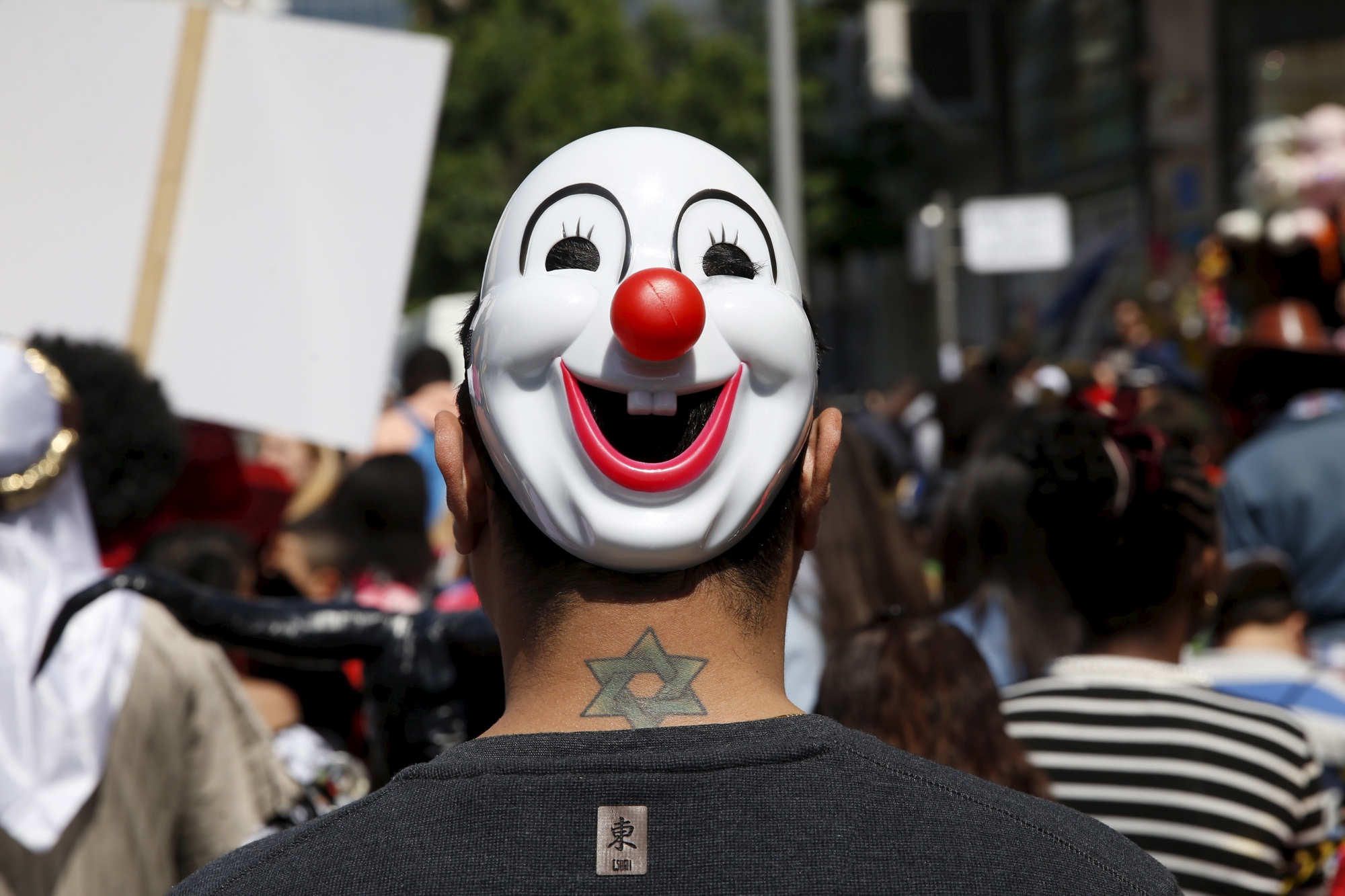 A man wearing a mask takes part in a parade marking the upcoming Jewish holiday of Purim outside the Bialik Rogozin school in Tel Aviv, Israel