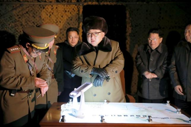 North Korean leader Kim Jong Un talks with officials at the ballistic rocket launch drill of the Strategic Force of the Korean People's Army (KPA) at an unknown location, in this undated photo released by North Korea's Central News Agency (KCNA) on March 11, 2016.