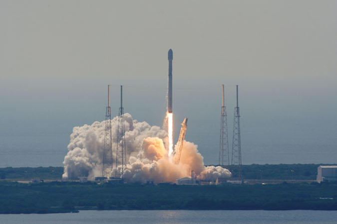 As seen from VAB roof at NASA Kennedy, Falcon 9 rocket lifts off at 10:29 a.m. EDT with Eutelsat 117 West B and ABS 2A comms satellites. Photo: SpaceFlightNow.