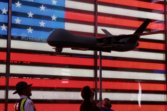 An official instructs two protesters to lower their Reaper drone model as they take part in a protest in Times Square NYC, May 24, 2016. REUTERS