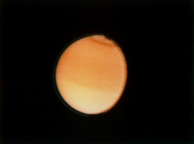 This Voyager 2 photograph of Titan, taken Aug. 23, 1981 from a range of 2.3 million kilometers (1.4 million miles), shows some detail in the cloud systems on this Saturnian moon. The southern hemisphere appears lighter in contrast, a well-defined band is seen near the equator, and a dark collar is evident at the north pole. All these bands are associated with cloud circulation in Titan's atmosphere. The extended haze, composed of submicron-size particles, is seen clearly around the satellite's limb. This image was composed from blue, green and violet frames.