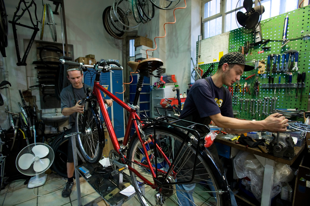 Two men working in a Bicycle repair shop, with tools of the trade.