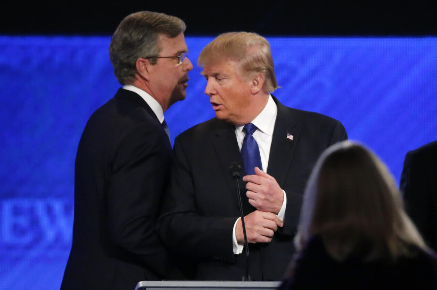 Governor Jeb Bush whispers to rival candidate Donald Trump as he passes behind him at the conclusion of the Republican U.S. presidential candidates debate on February 6, 2016. REUTERS