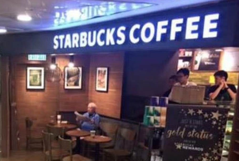 Man enjoys coffee in a flooded Starbucks