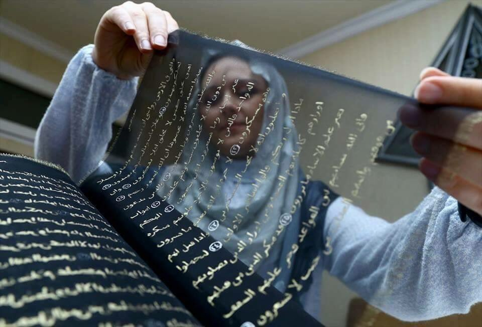 Quran hand-lettered in gold on transparent black silk