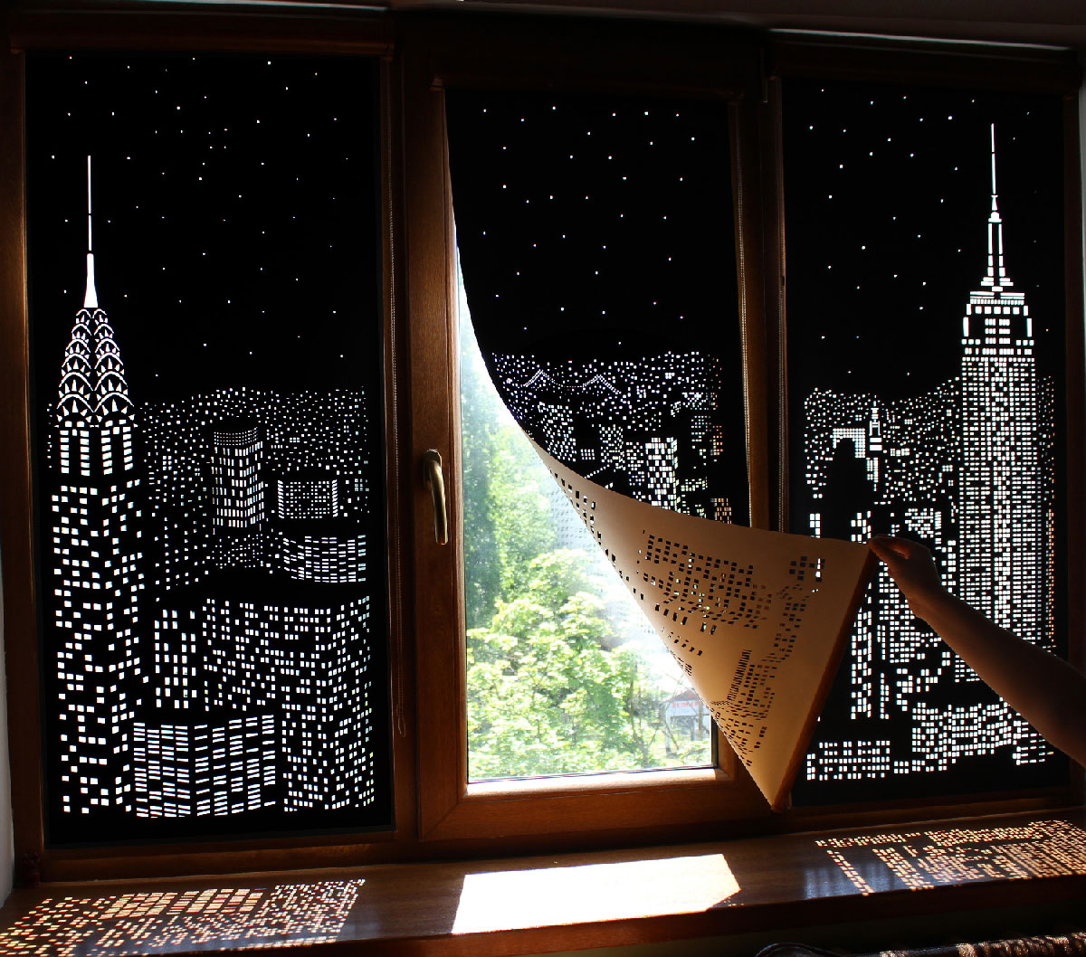 """""""Hole Roll"""": blackout curtains with trompe l'oeil cityscapes cut into them"""