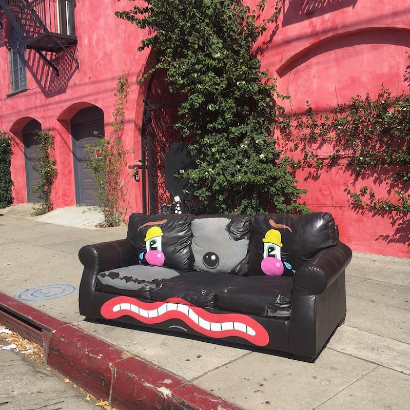 Street artist turns curbside furniture and electronics into sad clowns