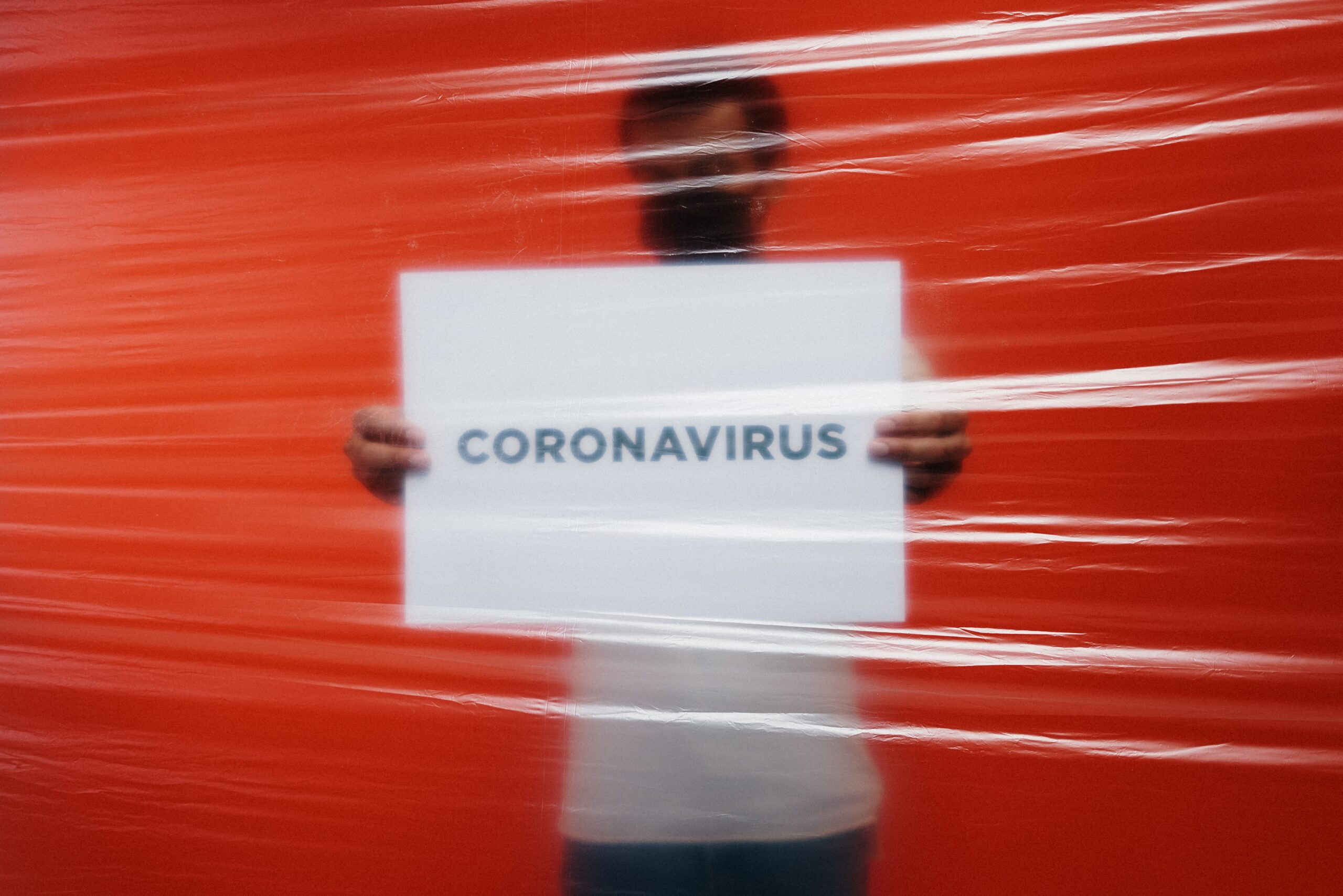 Right-wing websites are weighing the pros and cons of letting people die from coronavirus to help the economy Man-behind-a-plastic-holding-a-poster-of-coronavirus-3952185-scaled